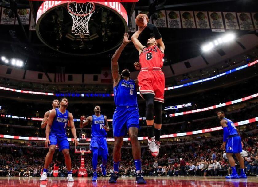 Zach LaVine (d), escolta de los Bulls de Chicago, dispara sobre el centro DeAndre Jordan (d) de los Dallas Mavericksdurante el partido de baloncesto de la NBA entre los Dallas Mavericks y los Chicago Bulls en el United Center de Chicago, Illinois, EE. UU.. EFE