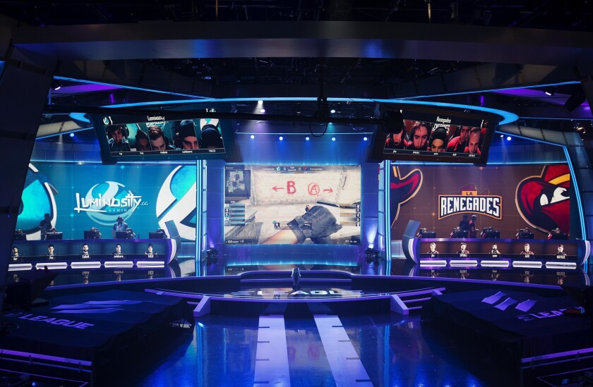 A screen, center, shows a professional video game competition between teams sitting on either side. Unionization of players is a big topic in the industry after several years of fast growth.