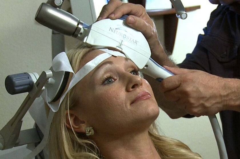Kelsey Popa, a patient with Dr. Scott Farmer in Orlando, Fla., uses transcranial magnetic stimulation, a treatment which delivers magnetic pulses to the brain and is one of the newer treatments for migraines.
