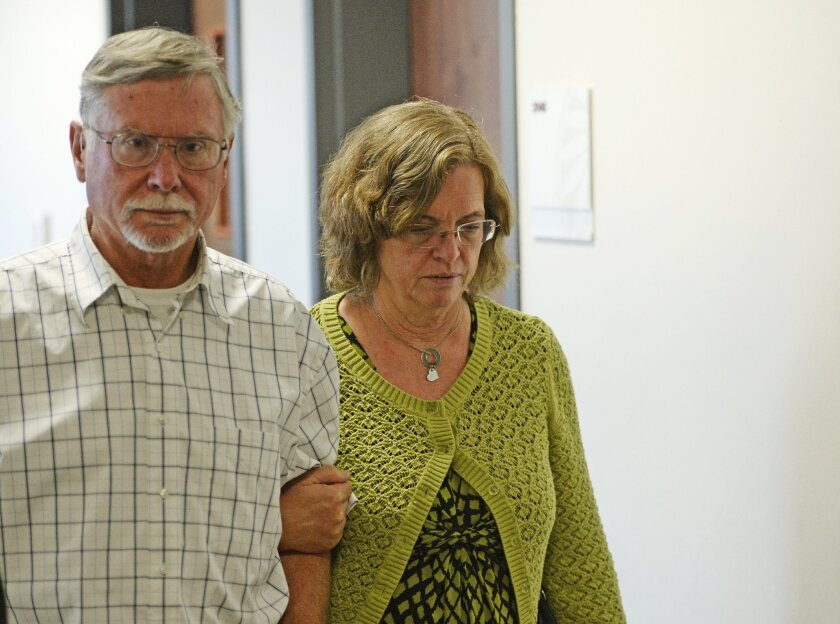 Robert and Arlene Holmes, parents of Aurora theater shooting suspect James Holmes, walk from the courtroom at the Arapahoe County Justice Center for a hearing in the 2012 Colorado movie theatre shooting case, July 22, 2014, in Centennial, Colo. The court will look at setting a new trial date in the