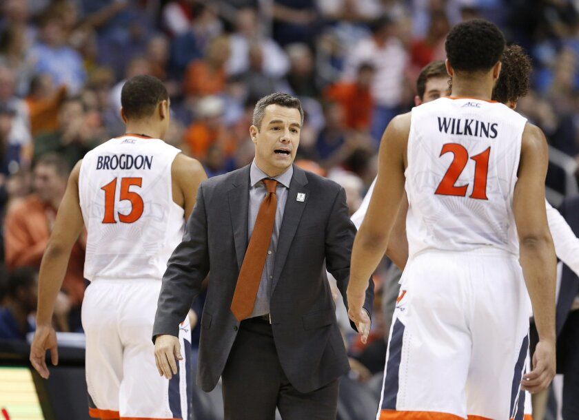 Virginia coach Tony Bennett welcomes guard Malcolm Brogdon (15) and forward Isaiah Wilkins (21) back to the bench during the second half of an NCAA college basketball game against Georgia Tech in the Atlantic Coast Conference men's tournament in Washington on Thursday, March 10, 2016. Virginia defe