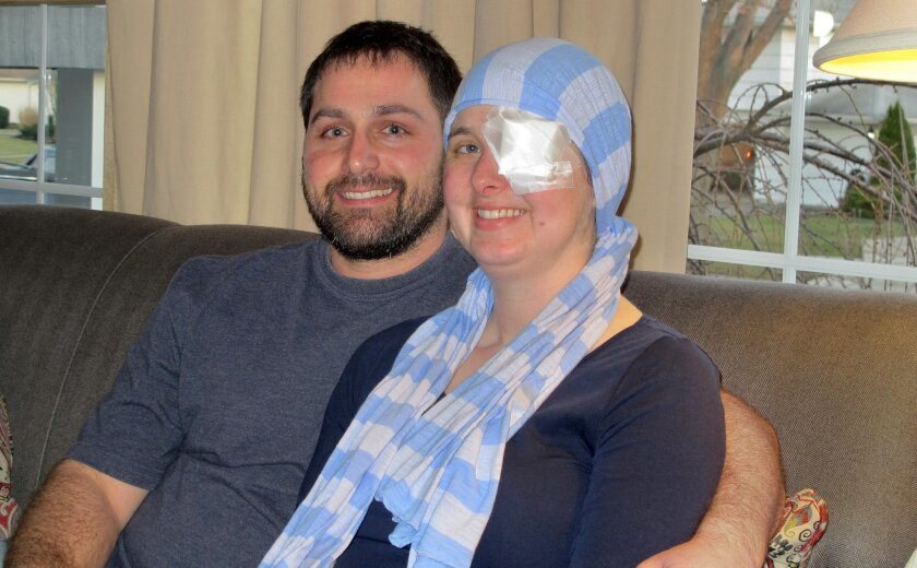 In this March 11, 2016 photo, Kim and Phil Vaillancourt are interviewed at their home in Tonawanda, N.Y. Shortly after learning she was pregnant, Kim was diagnosed with aggressive brain cancer, and was rushed into surgery to remove two tumors that doctors said could have soon killed her. She wears an eye patch now to improve her vision, and a scarf because some of the hair on her head was shaved, but is postponing the chemotherapy and radiation, considered her best defense against the cancer, until after the baby's birth. (AP Photo/Carolyn Thompson)