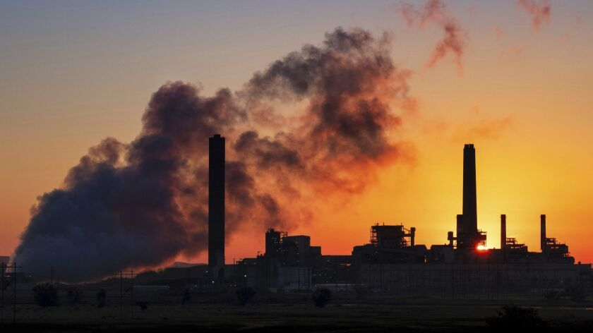 A coal-fired power plant is silhouetted against the morning sun in Glenrock, Wyo.