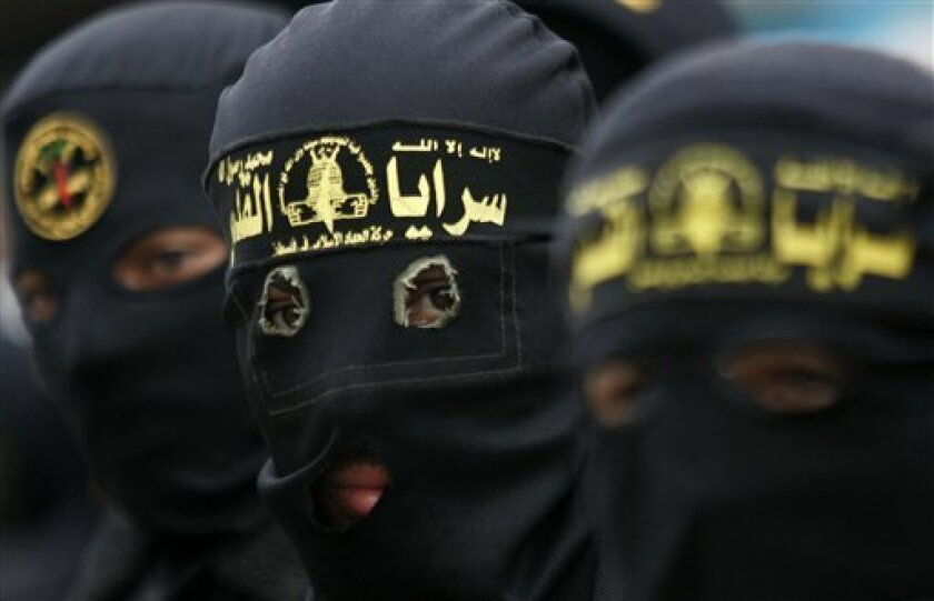Masked Palestinian militants are seen during an Islamic Jihad rally in Bureij, central Gaza Strip, Friday, Dec. 26, 2008. A projectile fired by Palestinian militants fell short of its target in Israel on Friday, striking a house in northern Gaza and killing two schoolgirls. The attack came as Israe