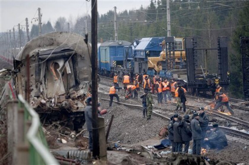 Investigators and rescue workers are seen amid wreckage and damaged coaches at the site of a train derailment near the town of Uglovka, some 400 km (250 miles) north-west of Moscow, Russia, Saturday, Nov. 28, 2009. An express train carrying hundreds of passengers from Moscow to St. Petersburg derailed, killing dozens of people and injuring scores of others in what may have been an act of sabotage, Russian officials said. (AP Photo/Ivan Sekretarev)