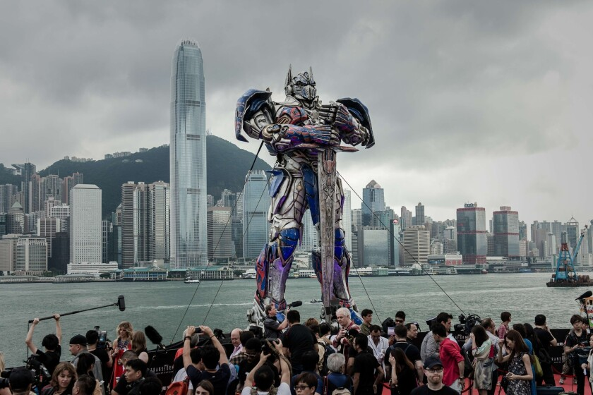 """A 20-foot-tall Optimus Prime figure is surrounded by journalists before the world premiere of """"Transformers 4"""" in Hong Kong."""