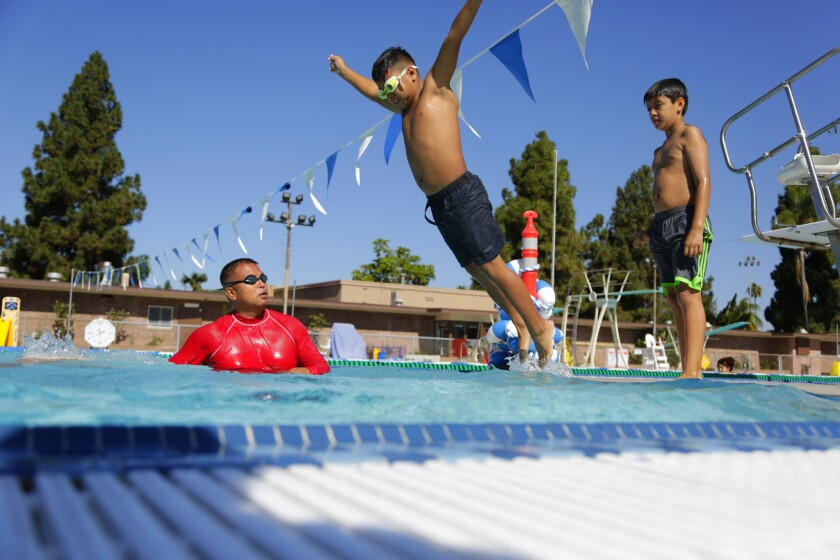 Swim instructor Antwan Lopez from Las Palmas Pool in National City observes as Christopher Galicia jumps into the pool.
