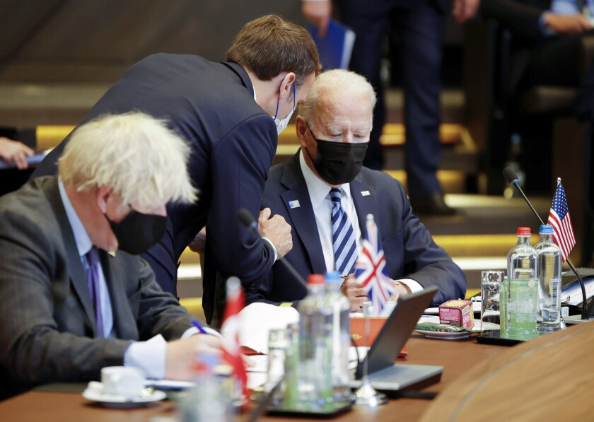 FILE - In this June 14, 2021, file photo French President Emmanuel Macron, center, speaks with U.S. President Joe Biden, right, during a plenary session at a NATO summit in Brussels. Ties between the United States and its oldest ally, France, have long been fraternal, but they've also been marked by deep French unease over their equality. French concerns about being the junior partner in the relationship boiled over last week when the U.S., Britain and Australia announced a new security initiative for the Indo-Pacific. (AP Photo/Olivier Matthys, Pool, File)