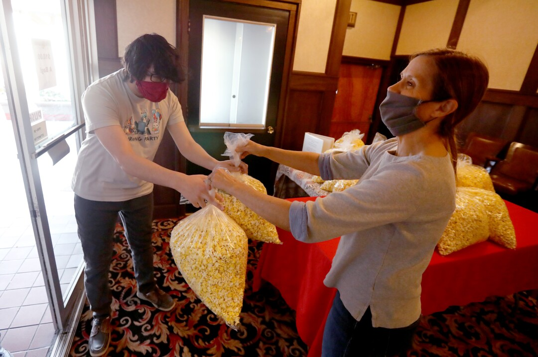 Bishop Theatre co-owner Holly Mullanix, right, serves up $10 bags of popcorn to a guest.