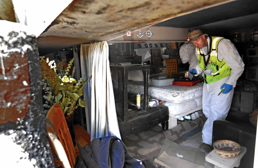 A city sanitation worker clears a living space under a pedestrian bridge over the Arroyo Seco during a sweep of homeless camps in northeast Los Angeles.