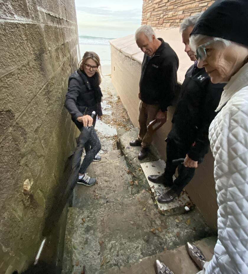 La Jolla resident Jill Peters points with her umbrella at the location for a railing proposed by Members of Friends of the Spindrift Drive Beach Access, a citizens group that also includes Tom Grunow, Patrick Ahern and Dori McCue.