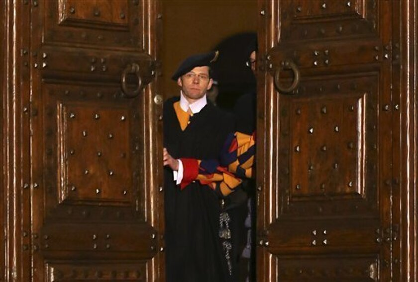"""Vatican Swiss guards close the main door of the papal residence in Castel Gandolfo, south of Rome, Thursday, Feb. 28, 2013. Benedict XVI greeted the faithful for the last time as pope on Thursday, telling tearful well-wishers that he is beginning the final stage of his life as """"simply a pilgrim,"""" h"""