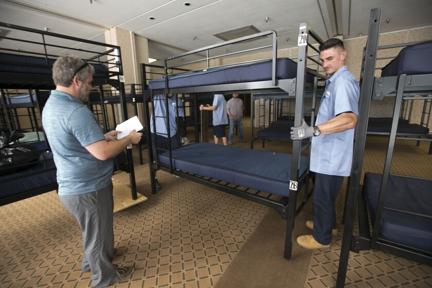 Paul Delessio, left, with Father Joes's Villages, works with mover Josh Mahaffey, right, with CNM Relocation Services to move bunk beds in to Golden Hall where a temporary bridge shelter is being set up to house homeless families that are currently in a tent that has to be moved to make way for development. The plan is to move the tent then move the people back in to it in late June.