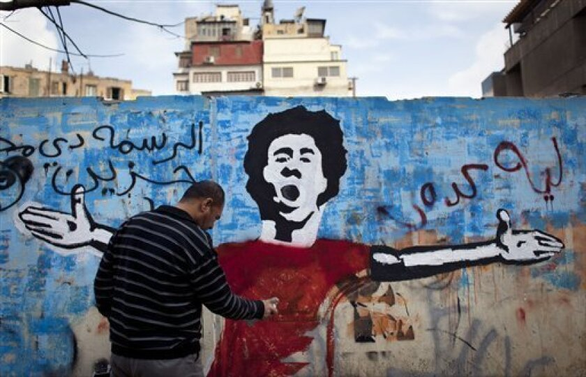 """An Egyptian activist paints a mural depicting a slain activist with Arabic that reads """"why did you do this? this is very sad,"""" on a wall in Tahrir Square, Cairo, Egypt, Tuesday, Feb. 19, 2013. An ultraconservative Islamist adviser to Egypt's president resigned Monday in solidarity with a fellow aide who was fired amid allegations of abuse of office. (AP Photo/Nasser Nasser)"""