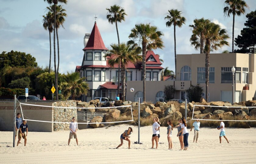 Beachgoers play volleyball across the street from a home known as The Livingston House, aka, The Baby Del sits. Originally built in San Diego in 1887, it was moved to Coronado in 1983 and its architecture is very similar to the Hotel Del Coronado, which was also built in 1887.