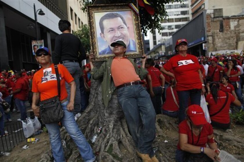 A supporter of Venezuela's acting President Nicolas Maduro leans against a tree under a poster of late President Hugo Chavez outside the national electoral council where Maduro registered his presidential candidacy in Caracas, Venezuela, Monday, March 11, 2013.  Presidential elections were announce