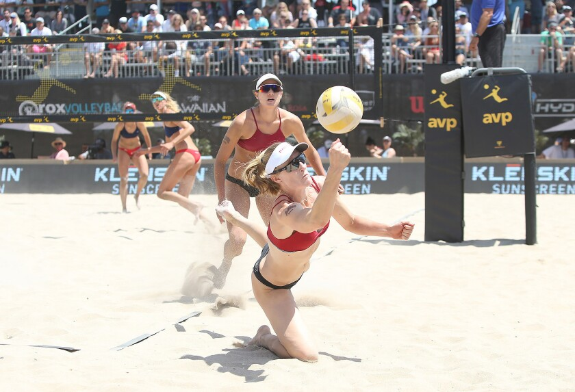 Emily Day runs down a deep ball still in play as teammate Betsi Flint looks on during a match at the Huntington Beach Open.