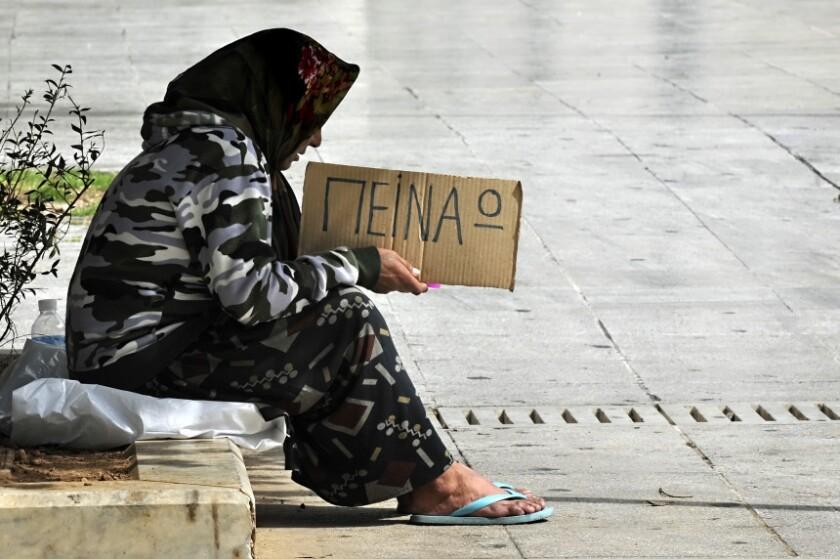 Una indigente sostiene un letrero en el que se lee 'Tengo hambre', en griego, en el centro de Atenas. El desempleo en Grecia alcanza ya al 25 por ciento de su población.