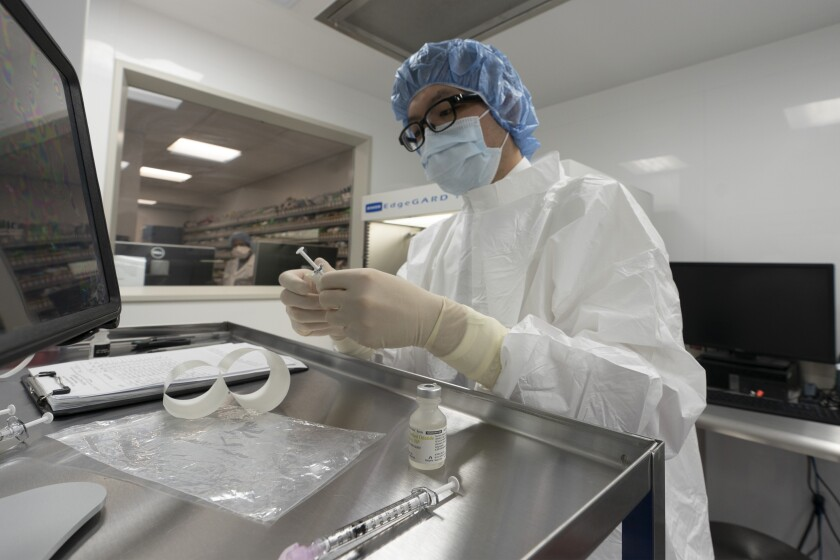 A pharmacist at Mount Sinai Queens hospital labels syringes in a clean room where doses of COVID-19 vaccines will be handled.