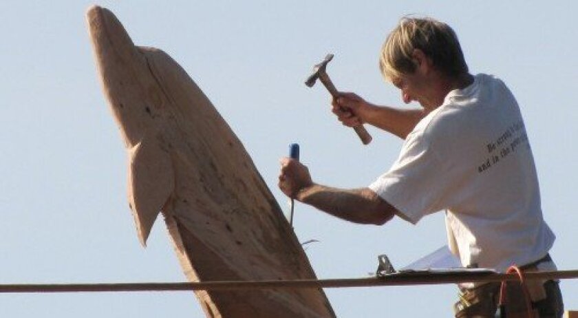 Andrew Cullum carves a dolphin from a 15-foot stump located near the bluffs on 10th Street in Del Mar. Courtesy photo
