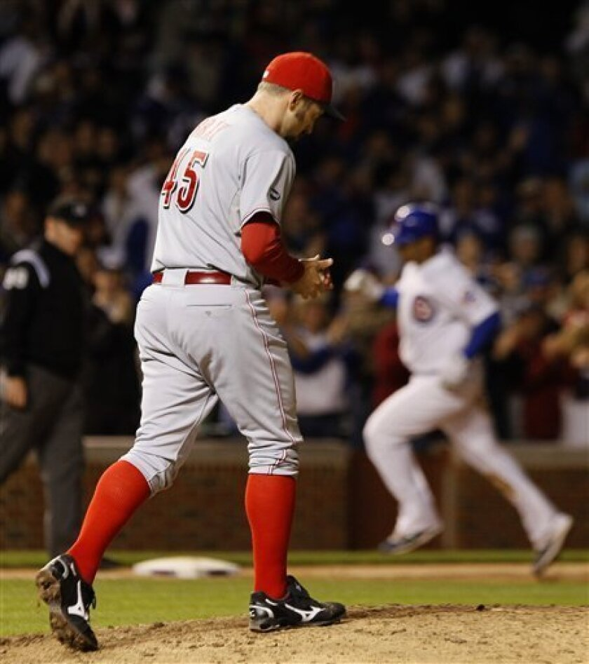 Cincinnati Reds relief pitcher Bill Bray, left, returns to the mound after giving up a three-run home run to Chicago Cubs first baseman Carlos Pena, right, also scoring Starlin Castro, and Aramis Ramirez, during the eighth inning of a baseball game and Cubs' 6-3 win Wednesday, Sept. 7, 2011 in Chicago. (AP Photo/Charles Rex Arbogast)