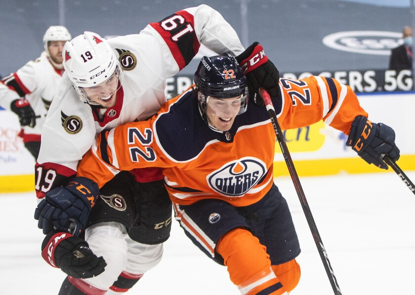 Edmonton Oilers' Tyson Barrie (22) and Ottawa Senators' Drake Batherson (19) battle for the puck during first-period NHL hockey game action in Edmonton, Alberta, Sunday, Jan. 31, 2021. (Jason Franson/The Canadian Press via AP)