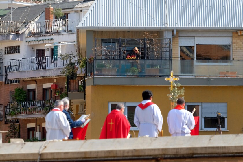 A person on a balcony follows the celebration of Palm Sunday Mass on the roof of the church of San Pio X in Rome on Sunday.
