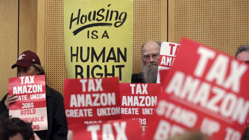 Members of the public look on at a Seattle City Council before the council voted to approve a tax on
