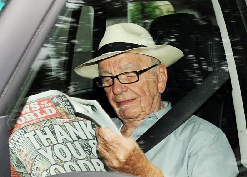 Rupert Murdoch is shown reading the last edition of the News of the World newspaper on July 10, 2011.