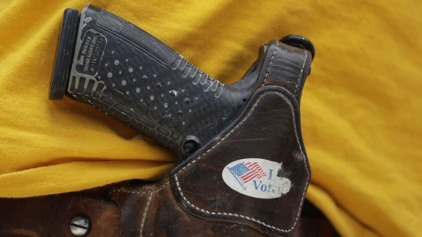 FILE - In this April 14, 2018 file photo, a man wears an unloaded pistol during a pro gun-rights ral