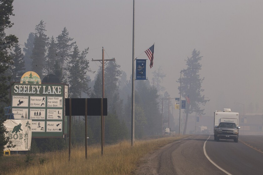 A pickup truck pulls a camper through the wildfire smoke in Seeley Lake, Mont., during the 2017 fire season.