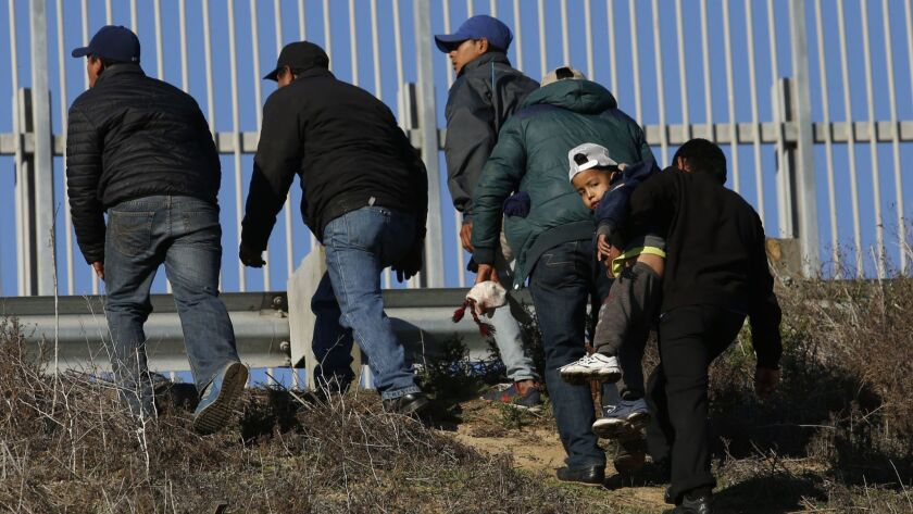 Honduran migrants who plan to turn themselves over to U.S. Border Patrol agents walk up an embankment after climbing over the U.S.-Mexico border wall from Playas de Tijuana, Mexico, on Dec. 12 2018.