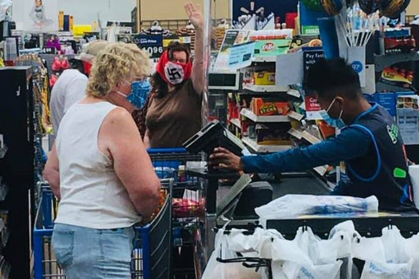 A woman wearing a swastika mask gestures to other Walmart shoppers in Marshall, Minn., on Saturday.