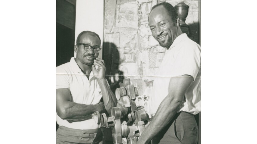 Artist Noah Purifoy, left, with Judson Powell, photographed at the Watts Towers Art Center in 1966. That same year, the pair organized a show inspired by the uprising that would go on to influence a generation of artists.