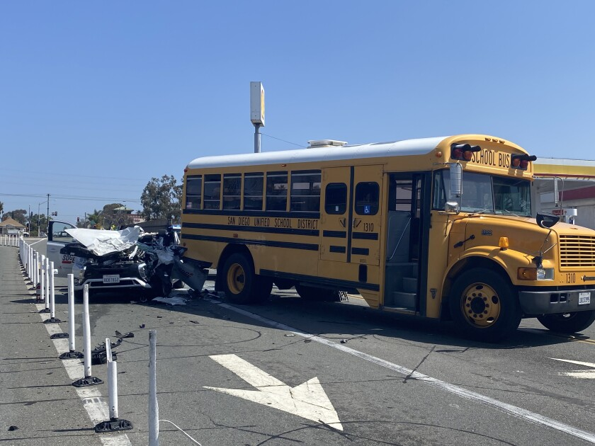 Badly damaged SDG&E van and back end of school bus