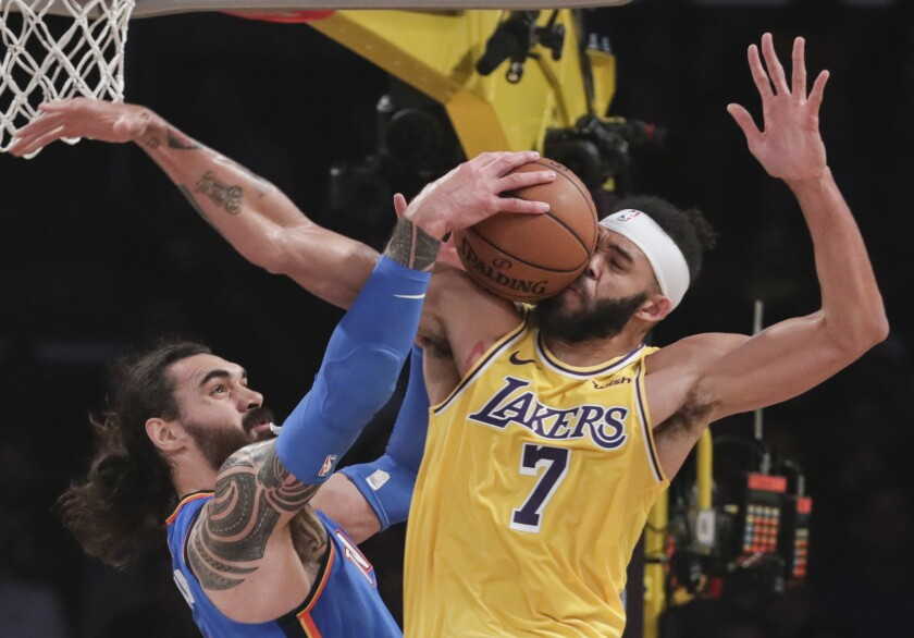Lakers center JaVale McGee (7) takes the ball off his face while battling Oklahoma City Thunder center Steven Adams (12) for a first half rebound at Staples Center on Tuesday.