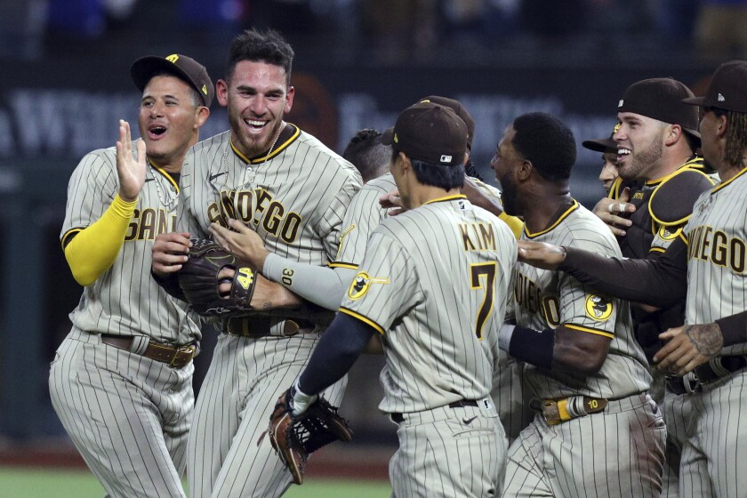 San Diego Padres starting pitcher Joe Musgrove, second from left, is mobbed by teammates after pitching a no-hitter against the Texas Rangers in a baseball game Friday, April 9, 2021, in Arlington, Texas. (AP Photo/Richard W. Rodriguez)
