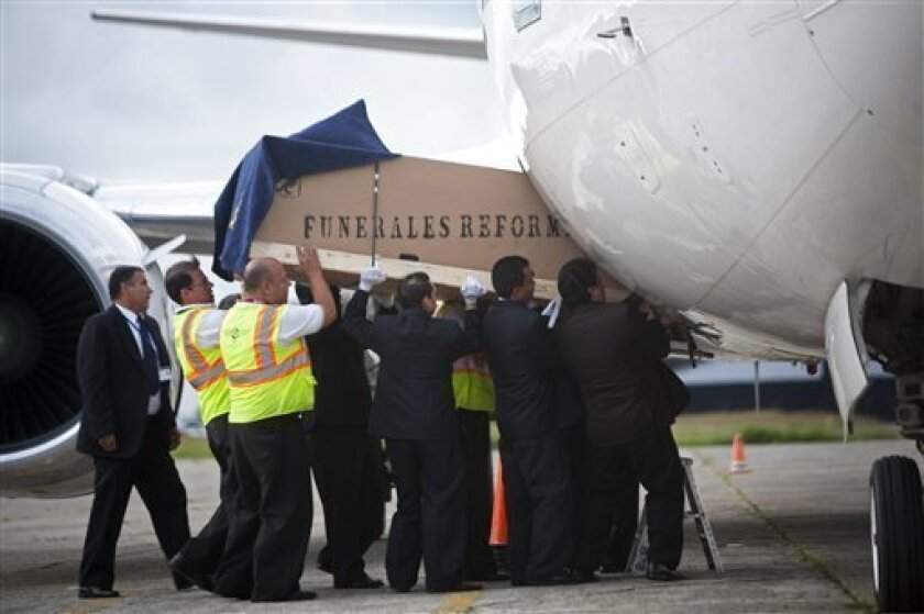 Funeral workers load into an airplane heading to Argentina, a coffin containing the body of murdered Argentine folk singer Facundo Cabral in Guatemala City, Monday, July 11, 2011. One of Latin America's most admired folk singers, Facundo Cabral, was killed Saturday July 9 when three cars loaded with gunmen ambushed the vehicle in which he was riding, prompting expressions of anguish from across the region. Authorities said the performer's concert promoter who was traveling with Cabral was apparently the target. (AP Photo/Rodrigo Abd)