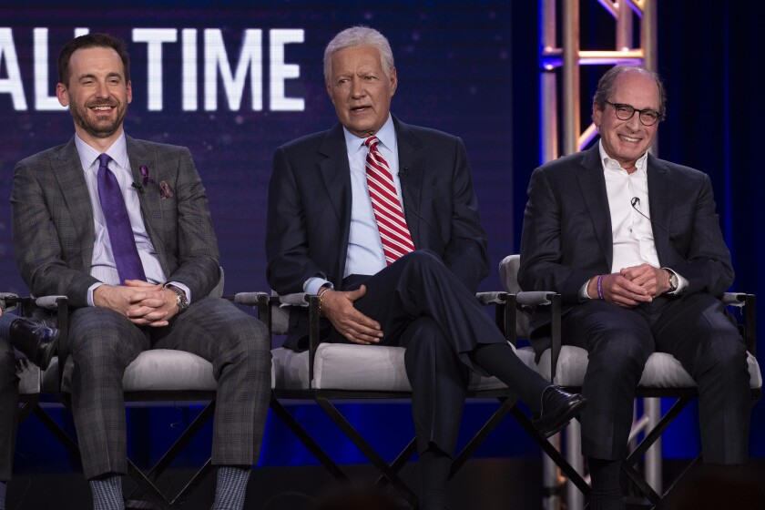 """Host Alex Trebek, center, with contestant Brad Rutter, left and executive producer Harry Friedman at the panel for """"Jeopardy! Greatest of All Time"""" at the Television Critics' Assn. press tour in Pasadena."""