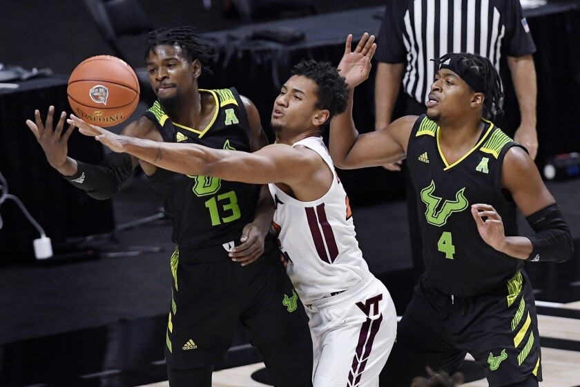 Virginia Tech's Keve Aluma, center, reaches between South Florida's Justin Brown, left, and South Florida's Michael Durr, right, for the ball in the first half of an NCAA college basketball game, Sunday, Nov. 29, 2020, in Uncasville, Conn. (AP Photo/Jessica Hill)