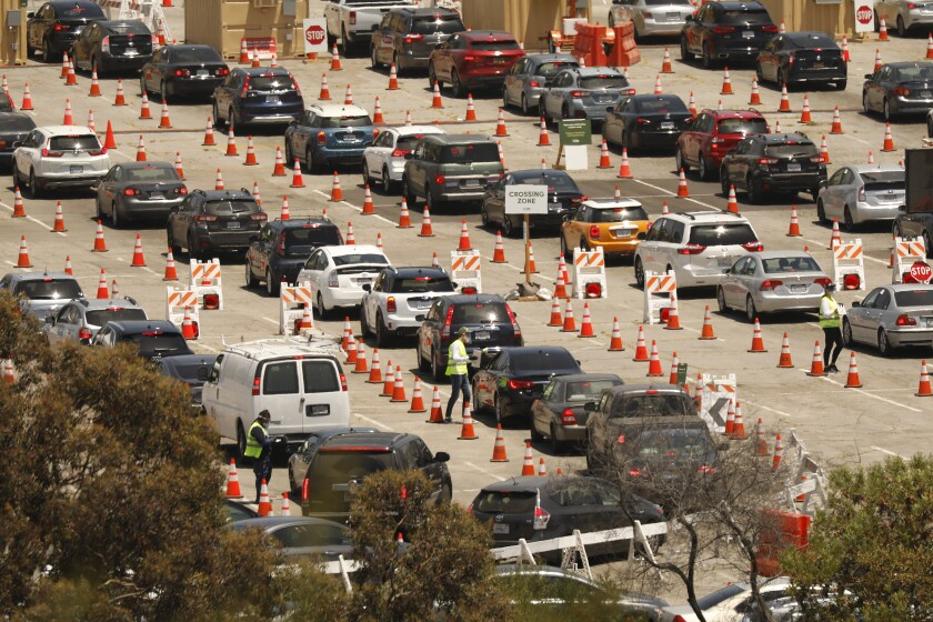 Coronavirus testing continues Wednesday at Dodger Stadium as drivers with an appointment wait in line.