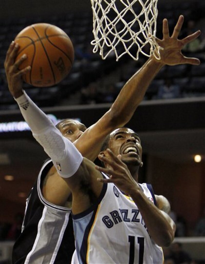 Memphis Grizzlies guard Mike Conley (11) shoots under pressure by San Antonio Spurs forward Tim Duncan, left, in the first half of an NBA basketball game on Monday, Feb. 6, 2012, in Memphis, Tenn. (AP Photo/Jim Weber)
