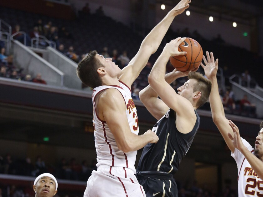 USC forward Nikola Jovanovic gets his hand in front of Colorado guard Eli Stalzer during a game Feb. 17 at the Galen Center.