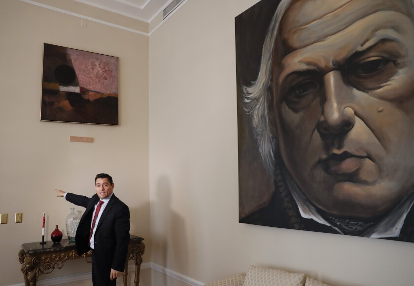 "In this Sept. 17, 2019, photo, Carlos Vecchio, an exiled politician who the U.S. recognizes as Venezuela's ambassador, points to a blank section of a wall where artwork once hung inside the Ambassador's residence in Washington. U.S. officials are investigating the possible looting from Venezuela of valuable European and Latin American artwork they believe is being quietly plundered by government insiders as Nicolas Maduro struggles to keep a grip on power. ""This is just the tip of the iceberg,"" Vecchio said. ""If this is what they've managed to do with some artwork at a single diplomatic mission, you can imagine what they've done inside Venezuela."" (AP Photo/Pablo Martinez Monsivais)"