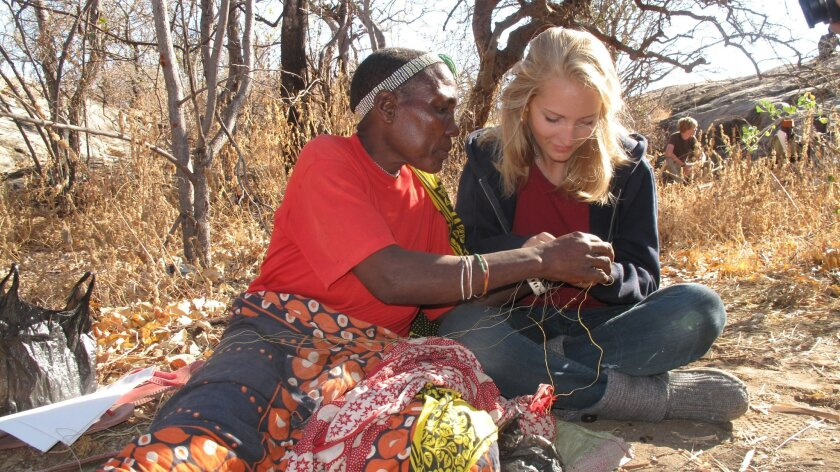 A Hadza woman teaches Natalie Brooks (right) a technique for beading tribal jewelry while Brooks was on a Grauer School Expedition to Tanzania. Courtesy photo