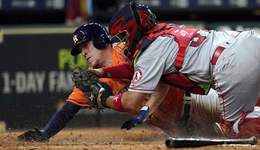 Houston's Myles Straw scores as Angels catcher Francisco Arcia tries to apply the tag during the eighth inning Friday