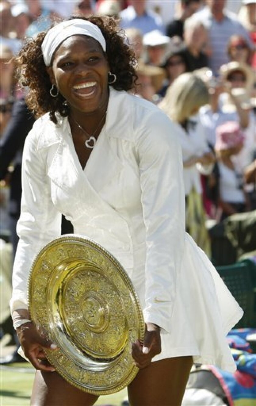 FILE - This is a July 4, 2009, file photo showing Serena Williams holding the championship trophy after defeating her sister, Venus, to win the women's singles final on the Center Court at Wimbledon. Her flair for theatrics and compelling back story brought new fans to the sport, which helped the WTA Tour achieve new levels of popularity. The U.S. Open final became a prime-time attraction, and Williams became a magazine cover celebrity. She also might be The Associated Press' Athlete of the Decade. (AP Photo/Kirsty Wigglesworth, File)