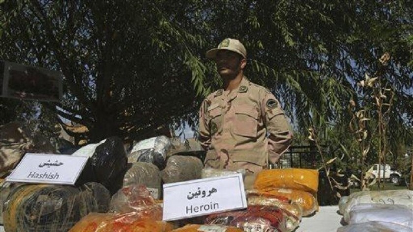 An Iranian police officer stands behind drugs seized from smugglers near the border with Afghanistan in 2014.