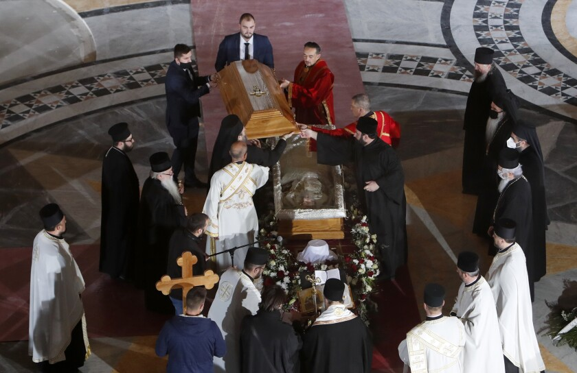 Serbian Orthodox Church leaders open the coffin of Patriarch Irinej during a procession in Belgrade, Serbia.