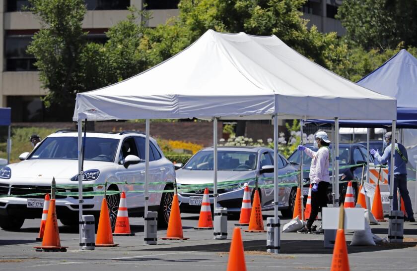Cars line up at a drive-through coronavirus testing site.